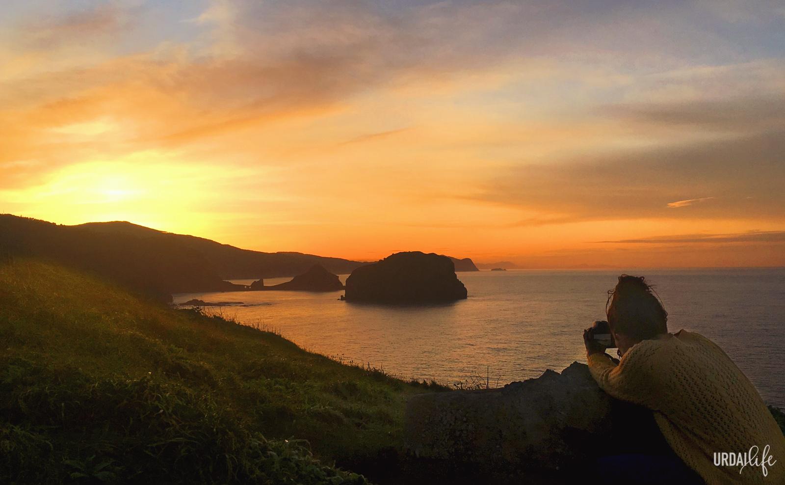 Fotografiar la puesta de sol desde Faro Matxitxako. San Juan de Gaztelugatxe al fondo.