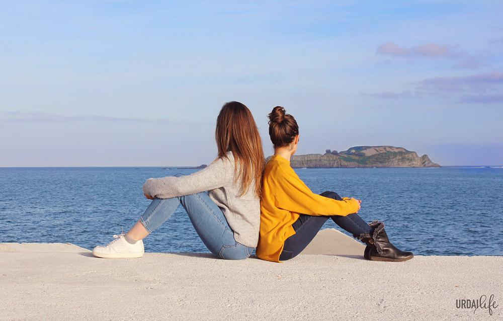 Sara y Nerea, fundadoras de Urdailife, en el rompeolas de Bermeo, frente a la isla de Izaro, en Urdaibai